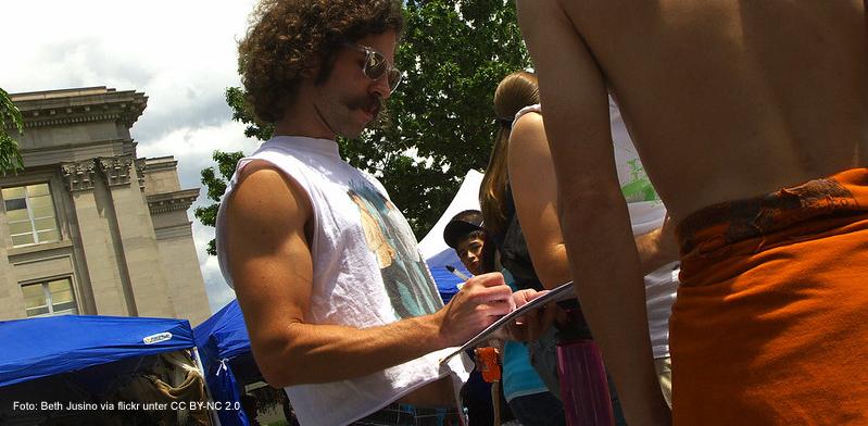 Ein lockiger Mann unterschreibt eine Petition auf einem öffentlichen Platz